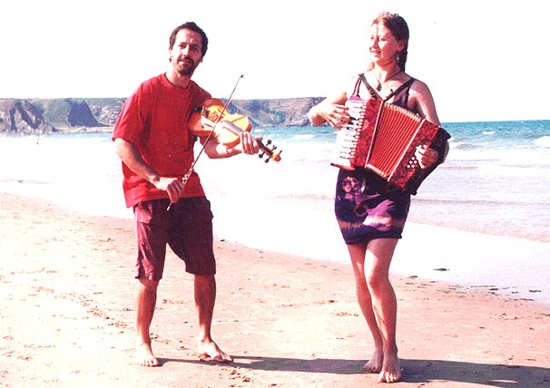 Photo of Phil & Sorrel on beach with instruments